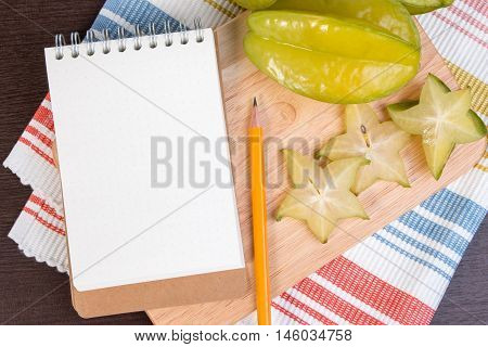 Star Apple Or Averrhoa Carambola And Notebook On Wooden Block. Fresh Star Apple Fruit And On Wood Ta