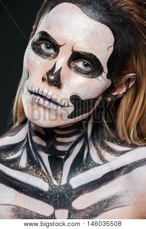 Closeup of woman with scared gothic makeup over black background
