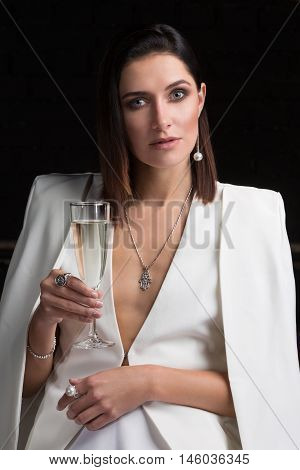 The girl in a white suit with a glass of champagne on a black background. Cute brunette celebrates in evening attire