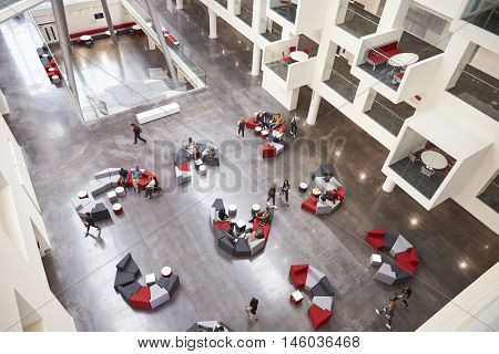 Students in the atrium of modern university building, aerial