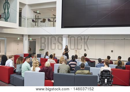 Students at a lecture in university atrium, back view