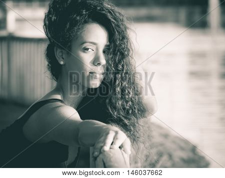 Latin woman looking at camera with outstretched hand monochrome