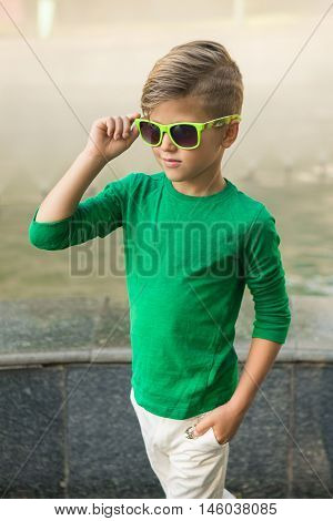 Stylish Little Boy In Sunglasses And Fashionable Clothes .