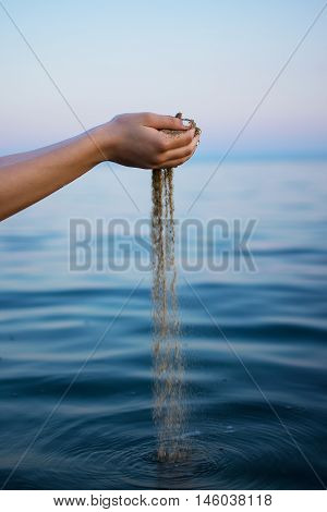 Woman Hands Holding Sand Close up Beach Outdoors Background. Sand Running Through Girl Hands in the Sea as a Symbol For Time Running.