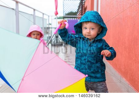 Little boy with colorful umbrella walking in the rain.