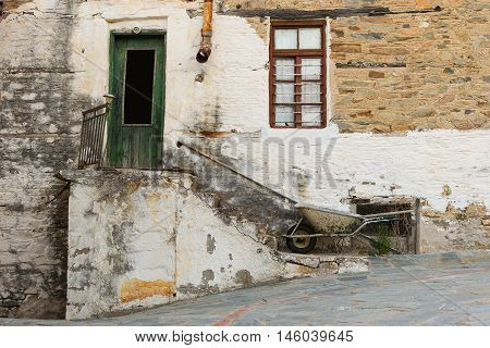 Old Stone House With Wooden Green Door and a Brown Painted Window, Staircase, Rusty Gutter and Wheelbarrow