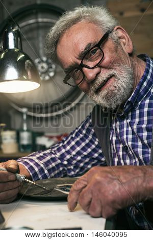 Smiling Senior Man Soldering Old Plate Behind Desk.