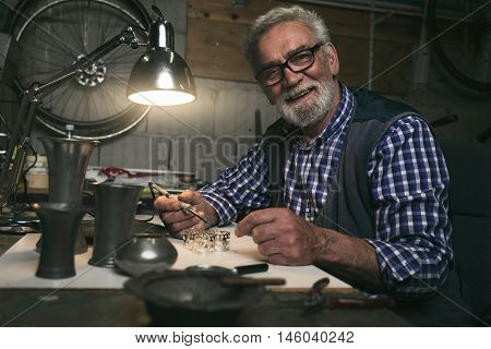 Smiling senior man soldering metal rings in workshop