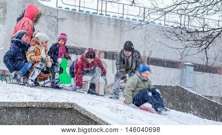 Yuzhnoukrainsk Ukraine - January 17 2016: Two days had the annual rate of snow wind 15-20 m s with gusts up to 28 m s the school canceled but it is not a barrier for children's fun. Children during the heavy snow and wind, have fun sledding.