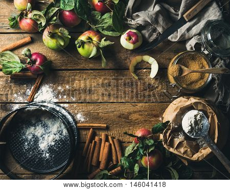 Ingredients for cooking apple pie. Fresh harvest apples with leaves, cinnamon, flour, sugar and baking mold over old rustic wooden background. Top view, copy space in center
