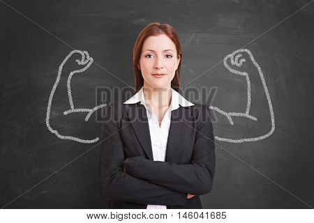 Successful self confident businesswoman with muscles drawn with chalk on a blackboard