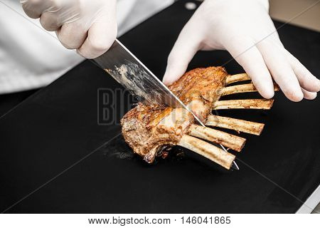 Rack of lamb sliced by chef in restaurant kitchen