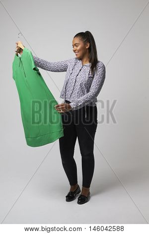 Studio Portrait Of Female Fashion Buyer Looking At Dress