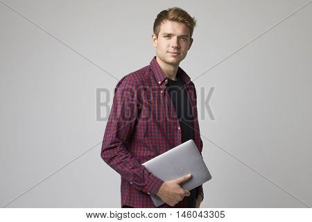 Studio Portrait Of Casually Dressed Businessman With Laptop