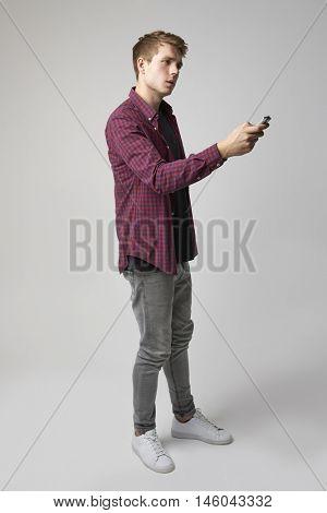 Studio Portrait Of Male Journalist With Digital Recorder