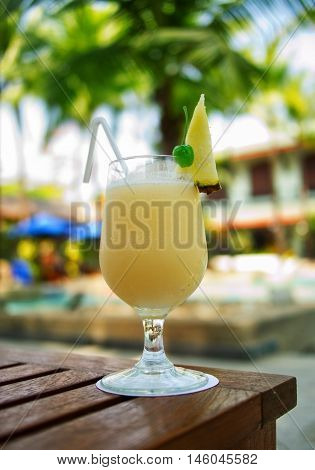 Yellow Pina Colada cocktail on a table on tropical island. Palm trees on background