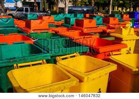 Garbage bins. Old colorful garbage bin on floor in park