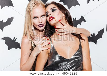 Two sexy young women with vampire halloween makeup posing over white background