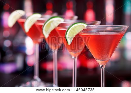 Row of Cosmopolitan cocktails shot on a bar counter in a nightclub. Shot in red light.