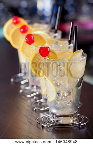 Row of four Tom Collins cocktails on a bar in a nightclub. Vertical shot