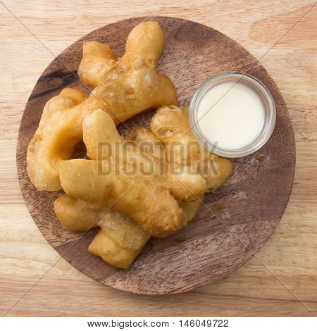 deep fried dough stick on the wooden plate with sweetened condensed milk