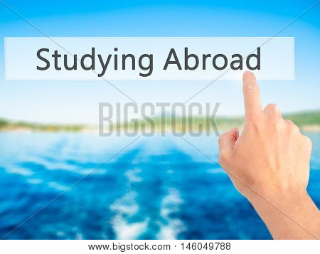 Studying Abroad - Hand Pressing A Button On Blurred Background Concept On Visual Screen.