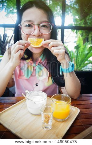 portrait of happy asian woman in a cafe with orange fruits against of a mouth like a smile,say cheese concept,happy with food concept,happy morning breakfast