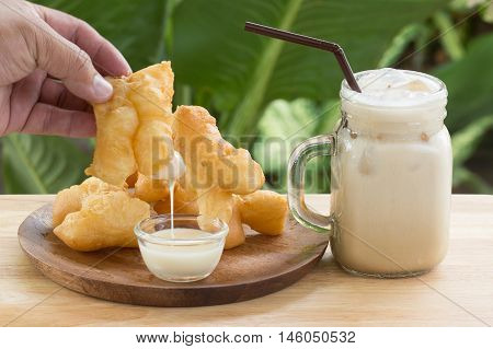hand holding deep fried dough stick deeping in sweetened condensed milk