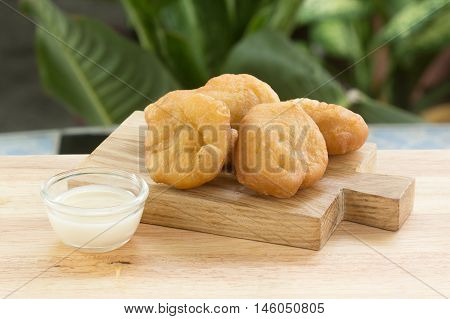 deep fried dough bun on the wooden plate with sweetened condensed milk