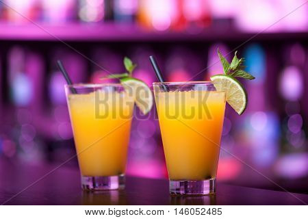 Two Harvey Wallbanger cocktail shot on a bar counter in a night club. Full lenght view. Blurred bottles on background. Horizontal shot