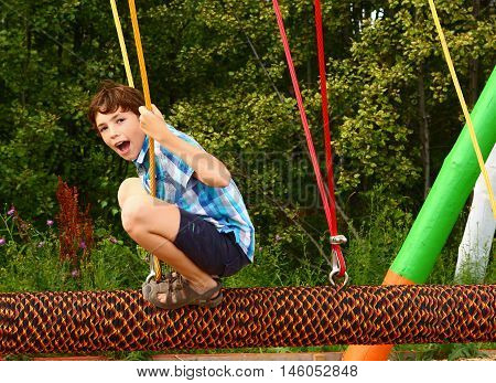 preteen happy boy in outdoor amusement park attraction log swing close up laughing smiling portrait
