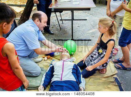 Zaporizhia/Ukraine- September  3, 2016: Charity festival for children - City of professions . Instructor demonstrates  lifesaving CPR techniques on mannequin. Emergency training for children.