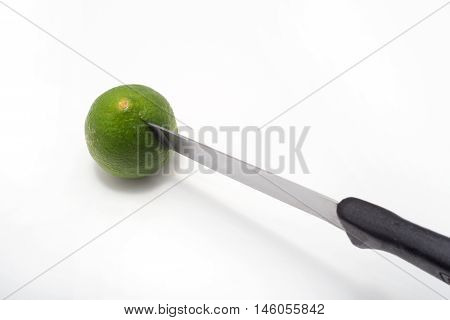 A green lemon is being stabbed by a knife on white background