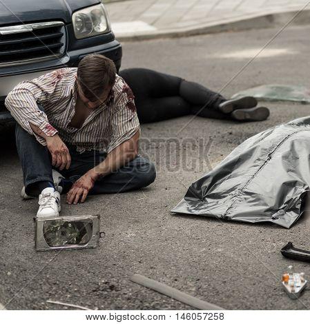 Injured Man Sitting On The Street
