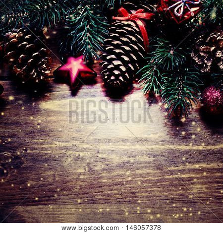 Christmas or New Year decoration background with fir tree branches pine cones balls and gifts on dark wooden board with copy space