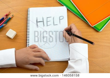 An image /poster covering the Social Issues of child abuse schoolchild in uniform at a desk asking for help by a written message saying Help with a sad face . Room for copy space and text