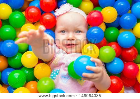 Baby girl lying down in colourful balls and reaching hand to go out