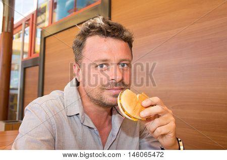 Man in a restaurant or diner eating a hamburger