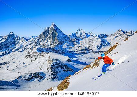 Full length of turn skier skiing on fresh powder snow with Matterhorn in Swiss Alps.