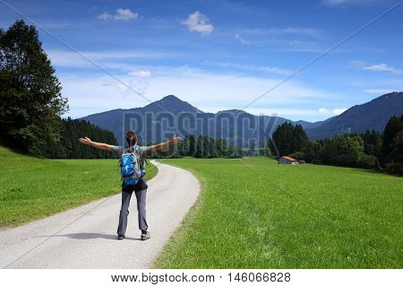 happy hiker is standing on a small road