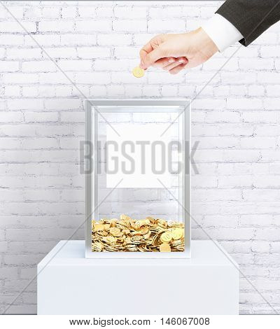 Businessperson hand putting coin into donation box with blank label. White brick wall background. Charity concept. Mock up 3D Rendering