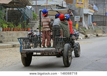 POKHARA, NEPAL - APRIL 2014 : Group of young boy sitting standing on a converted rotary hoe used as Nepali styled mini tractor on street in Pokhara, Nepal on 16 April 2014