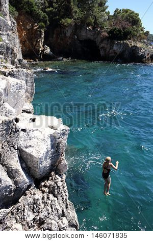young girl jumps into the blue ocean