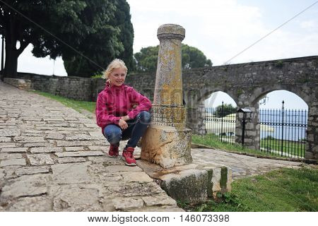 girl is sitting on an old pavement