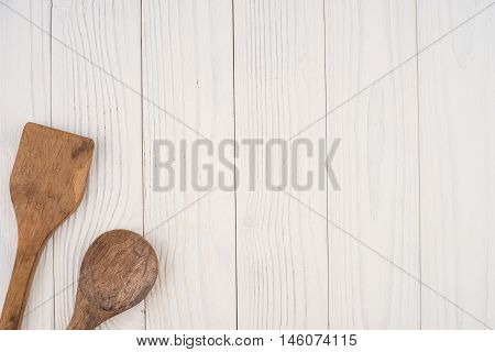 Wooden spoon and spatula on an old white table. Top view.