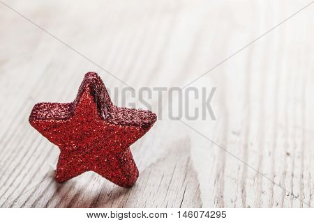 Small Red star on wooden background close-up