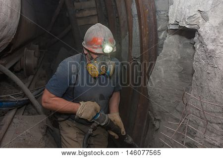 Miner in a respirator with a jackhammer in underground coal mines