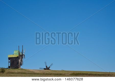 Landscape with windmills on the background of blue sky. On the hill there are two windmills. Due to the elevated position seen third windmill wings. Background