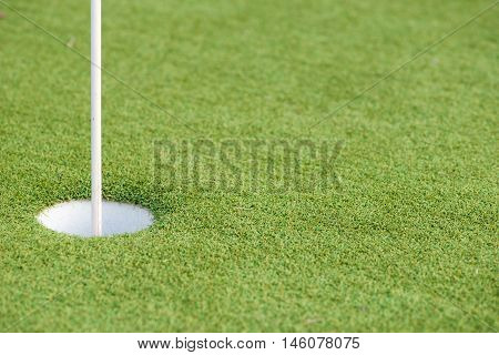 Close-up detail of a golf hole with a flagpole on artificial turf. Sports and recreation concept.