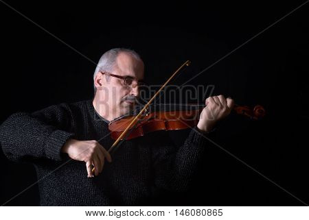 Portrait of a Caucasian man playing the violin in the darkness